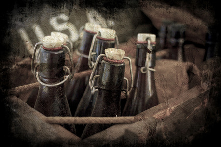 34504453 - old vintage beer bottles in a wooden crate with a grunge effect.