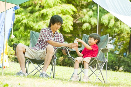 43859089 - father and son chatting sitting in a chair in the camping