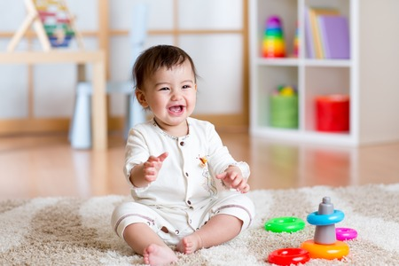 52541716 - cute cheerful baby playing with colorful toy pyramid at home