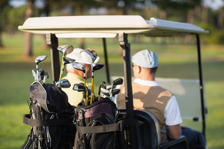 59498960 - rear view of golfer friends sitting in golf buggy on sunny day